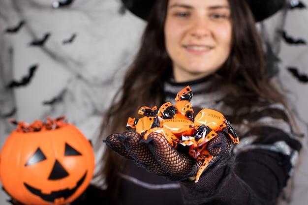 마녀 의상을 입은 한 여성이 할로윈이라는 글자가 새겨진 주황색 사탕을 들고 웃고 있습니다.