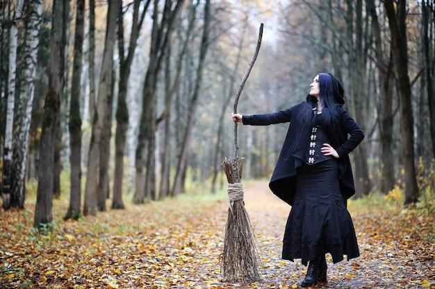 Женщина в костюме ведьмы в густом лесу на ритуале