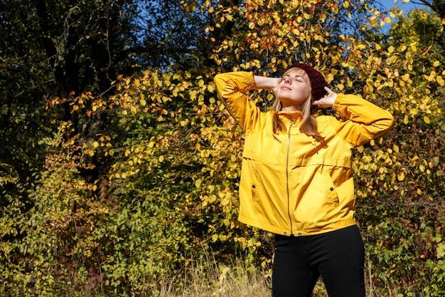 明るい日に秋の黄色の葉を背景に黄色のジャケットと赤い帽子をかぶった女性。秋の気分。横にテキスト用の空きスペース