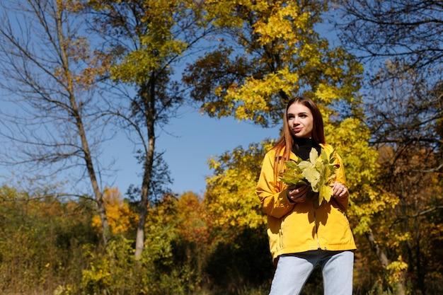 公園の散歩の明るい秋の背景に紅葉と黄色のジャケットの女性