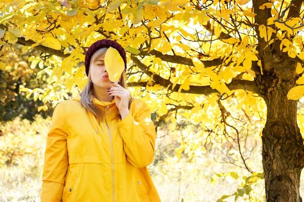 黄色いレインコートを着た女性が、紅葉を背景に紅葉で顔を覆っています。テキスト用の空き容量