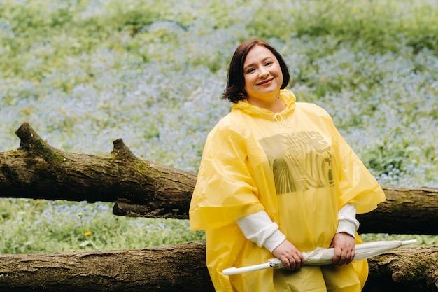 夏に森の倒木に傘をさした黄色いレインコートを着た女性が座っています。
