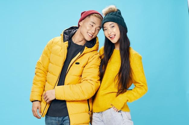 노란색 스웨터를 입은 여자와 따뜻한 모자를 쓴 파란색 배경의 젊은 남자. 고품질 사진