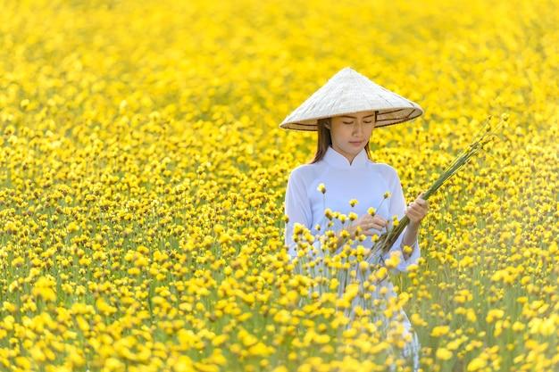 고대 베트남 민족 의상을 입은 여성이 노란 꽃 사이에 고리 버들 세공으로 만든 모자를 들고 서 있었다.