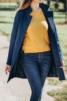 Женщина в осеннем пальто гуляет по городу