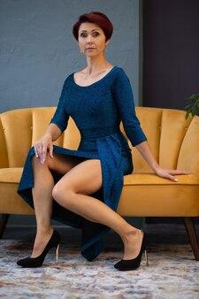 エレガントなドレスを着た女性が明るい黄色のソファに座っています。