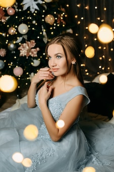 이브닝 블루 드레스를 입은 여성이 크리스마스 트리 근처에 앉아 꿈을 꾼다
