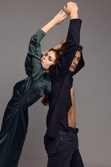 Женщина в вечернем платье и мужчина в костюме с поднятыми руками на сером фоне. фото высокого качества