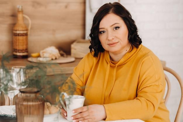 オレンジ色のパーカーを着た女性が、コーヒーを飲みながらキッチンのテーブルに座っています。
