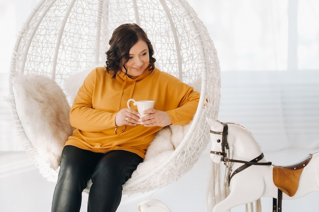 オレンジ色のパーカーを着た女性が珍しい椅子に座って、家でコーヒーを飲みます。