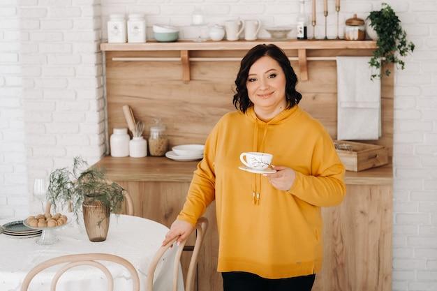 オレンジ色のスウェットシャツを着た女性が自宅のキッチンでコーヒーを飲みます。 Premium写真