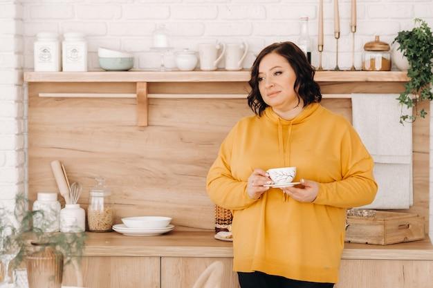 주황색 셔츠를 입은 여자가 집에서 부엌에서 커피를 마신다.