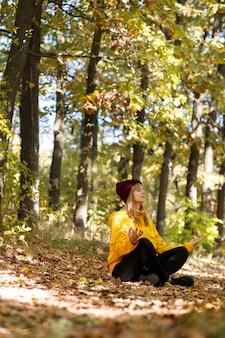 秋の服を着た女性が、静かな蓮華座の森に座っています。秋