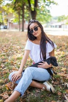 自然の中で犬を包む秋の服の女性