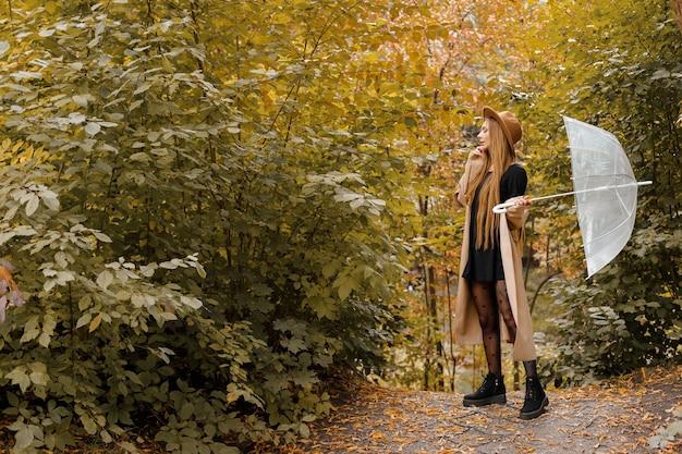Женщина в осенней верхней одежде с прозрачным зонтиком осенью. свободное место для текста