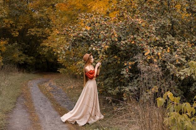 秋の森の美しい秋の服を着た女性。テキスト用の空き領域。ポスター秋