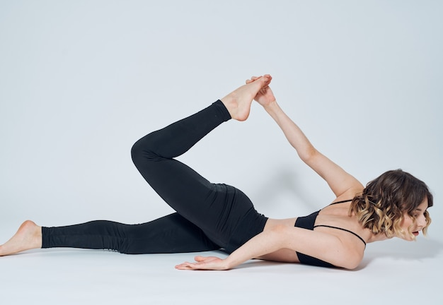 黒いレギンスを着た女性が床の明るい部屋で体操をしている。