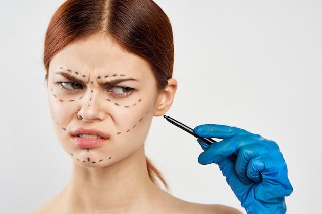 Женщина в синих перчатках держит в руках шприц и показывает на лицо операцию инъекции ботокса