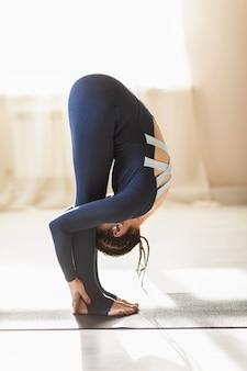 ヨガを練習している青いスポーツウェアの女性uttanasanaが立って前傾し、足で頭に触れた