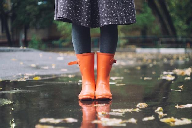雨の下で明るいピンクのゴム長靴(ゴム長靴)の女性。秋のコンセプト