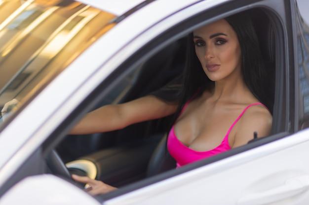 車内の女性がタッチスクリーンディスプレイのピンクのドレスオートマチックギアボックスでナビゲーションアプリケーションを選択します...