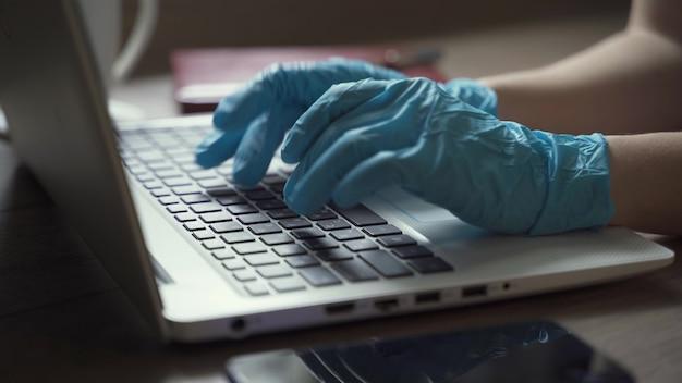 ノートパソコンで使い捨て手袋をはめた女性
