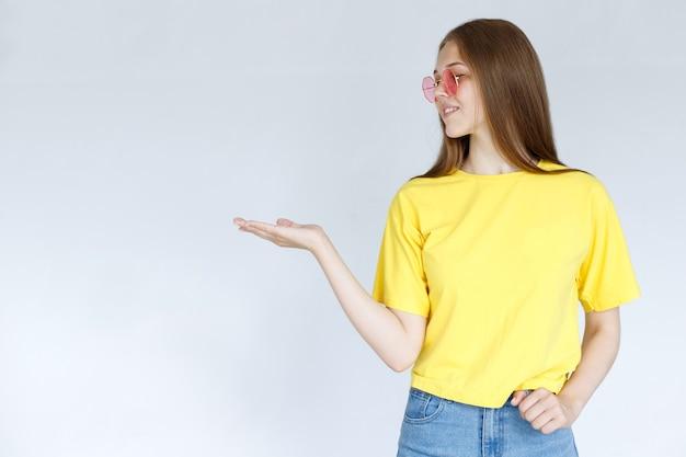 眼鏡をかけた女性と黄色のtシャツが灰色の背景に横向きに表示されます。テキストの場合