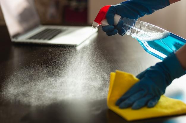 手袋をした女性が防腐剤をテーブルに置き、ナプキンで拭きます。 covid-19を含む、ウイルスや病気の蔓延を防ぐ手段