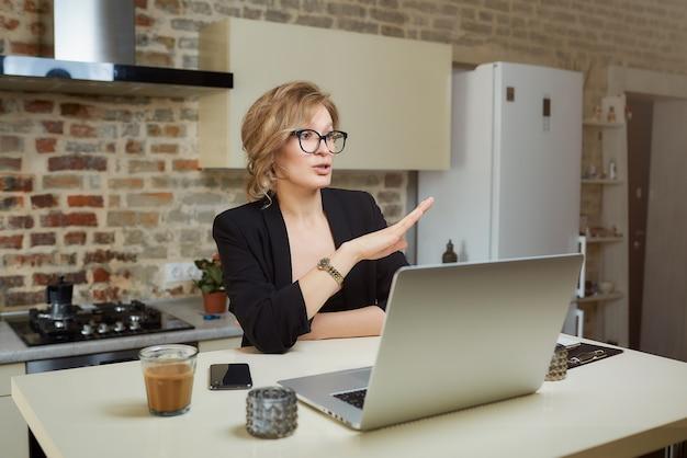 Женщина на ее кухне работает удаленно на ноутбуке. белокурая девушка в очках, gesturing во время разговора с коллегами в видео звонок у себя дома.