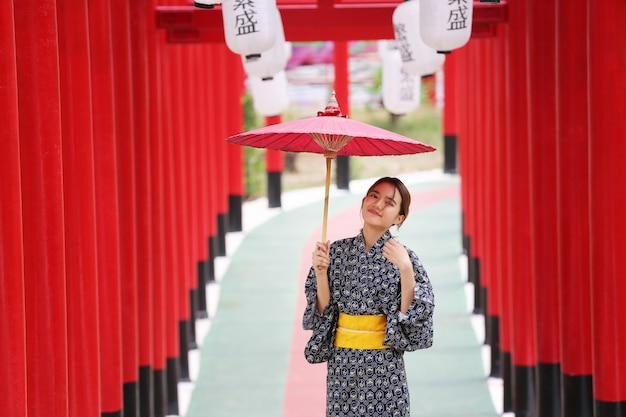 日本庭園の神社に傘をさして歩いている着物姿の女性。