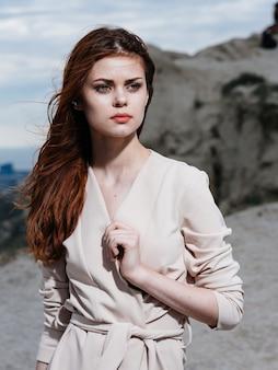 薄着の女性が山の岩の近くを自然の中で旅します。高品質の写真