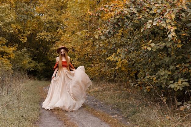 10月の散歩で長くてエレガントな秋の服を着た女性。テキスト用の空き容量