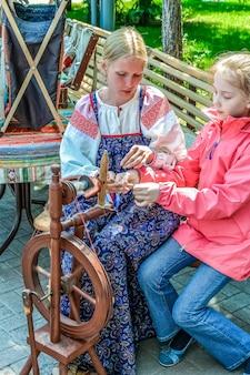 Женщина в национальной одежде учит девушку работать на ручной прялке
