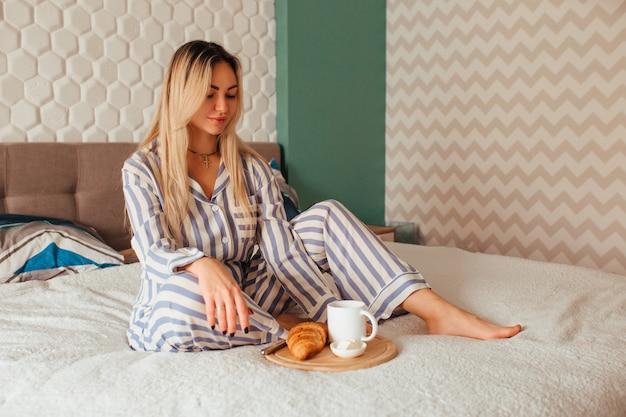 잠옷을 입은 여성이 침대에 크로와상과 함께 커피를 마신다.