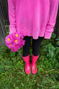 ピンクのブーツとピンクのセーターを着た女性が、美しいピンクの花の花束を手に持っています。女の子は通りに立っています。