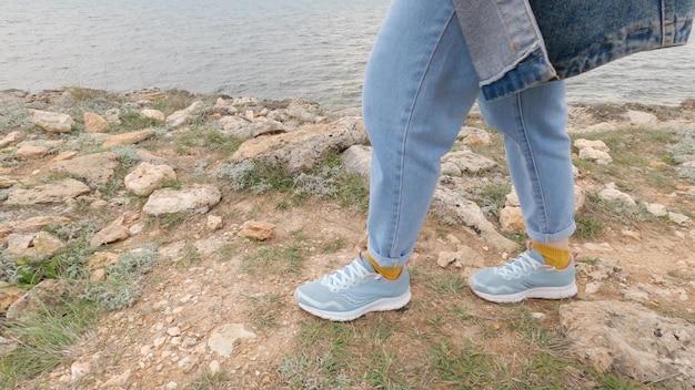 スニーカーを履いた女性が湖のほとりを歩いています。水の背景に女性の足のクローズアップ。海岸沿いを歩きます。 4k uhd