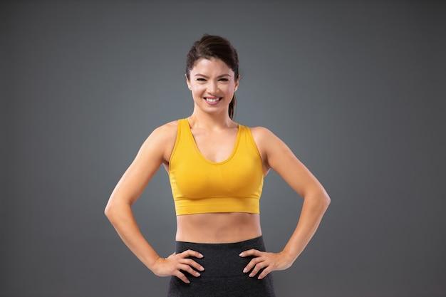 スポーツの女性。彼女の腰に手を置いて灰色の背景の前に立っている自信を持って大人のスポーティな女性の肖像画。スポーツウェア、健康的なライフスタイルと自然の美しさのフィットネスの女の子