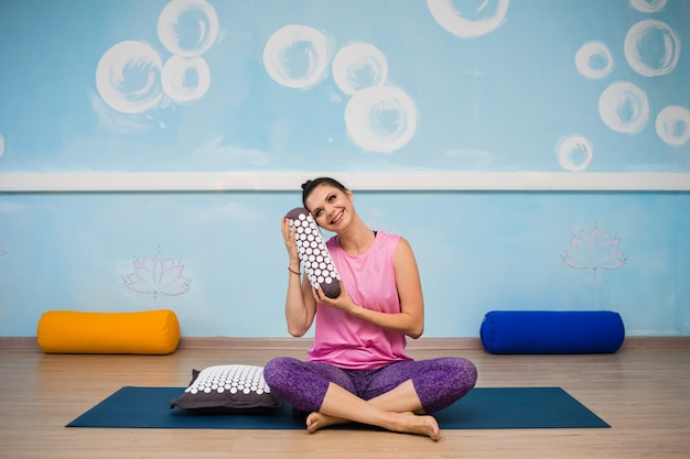 Женщина в спортивной одежде сидит на коврике с подушкой с иголками