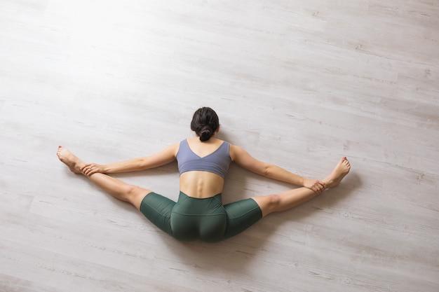 スポーツレギンスと短いtシャツを着た女性、ヨガの施術者が床に座ってサモカナサナのエクササイズを行い、体を前に傾けて横に分割します