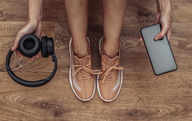 スポーツシューズを履いた女性が、床に座ってスマートフォンとワイヤレスヘッドホンを手に持っています。健康的なライフスタイルのコンセプト、トレーニング。上面図