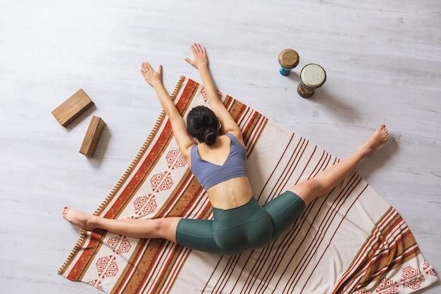 ヨガをしているスポーツウェアの女性が、体を前に傾けた状態で毛布の上に横に裂けて座っている間、サモカナサナ運動を行います