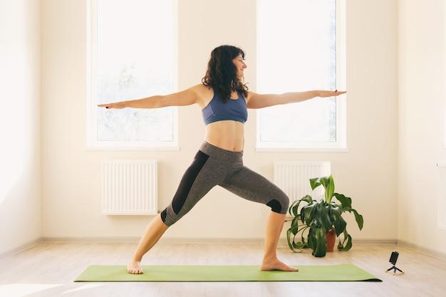 Женщина в спортивной одежде тренируется дома - девушка занимается фитнесом, наблюдая за тренировкой по видеосвязи
