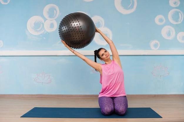 Женщина в спортивной одежде занимается фитболом на коврике в студии