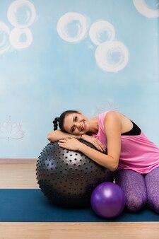 Женщина в спортивной одежде сидит с фитболом на коврике в студии