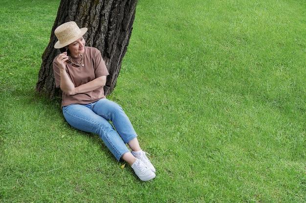 夏服を着た女性と麦わら帽子が芝生の木の近くに座って微笑んでいます。