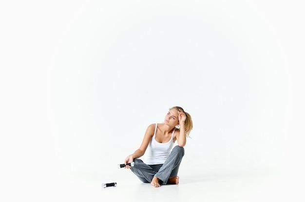 スウェットパンツを着た女性が床に座り、ダンベルを不快に見ている