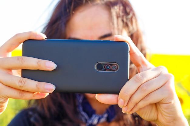 Женщина днем стреляет по телефону в поле