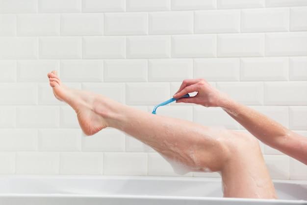 Женщина в ванной бреет ноги бритвой. крупный план руки с бритвой.