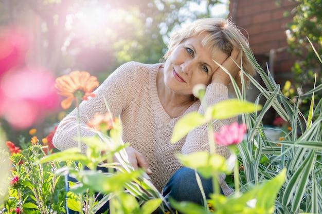 庭の女性が苗に花を選びます。中年の女性がカメラのレンズをのぞき込む。彼女は村で働いています。