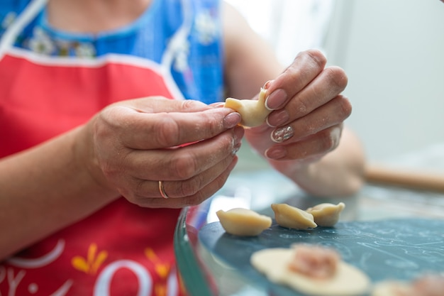 Женщина на кухне готовит пельмени из теста и мясного фарша крупным планом